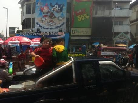 Thai Boy Throwing Water From a Truck During Songkran