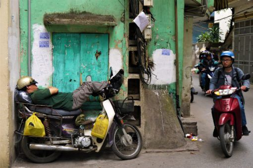 Vietnamese man napping on his motorbike