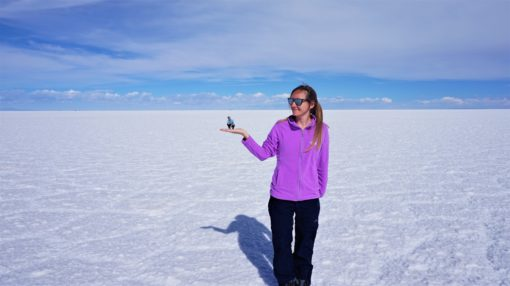 Salt flats perspective photo - big person holding a small one on the palm of their hand