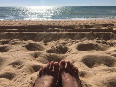 My feet in the sand down at the beach, contemplating our new site design