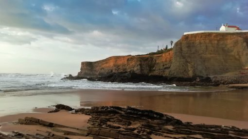 Beach and cliff topped with a church in the Algarve, Portugal