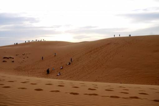Sand boarders and sunset seekers on the Red Sand Dunes Mui Ne