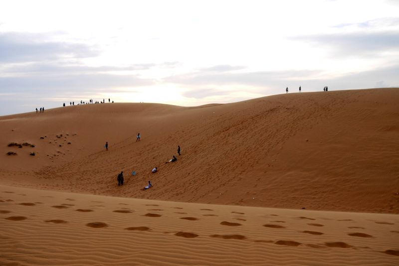 Sand boarders and sunset watchers on the Red Sand Dunes Mui Ne