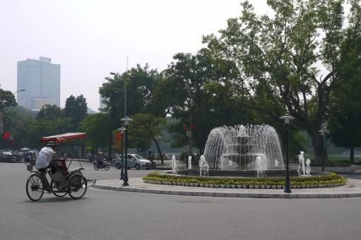 Cyclo driver and fountain in Hanoi's Old Quarter