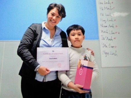 Melissa giving a prize to a Vietnamese student