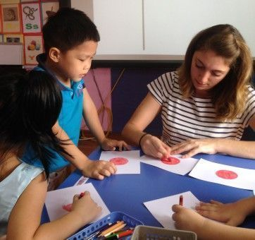 Hannah colouring with her Vietnamese students