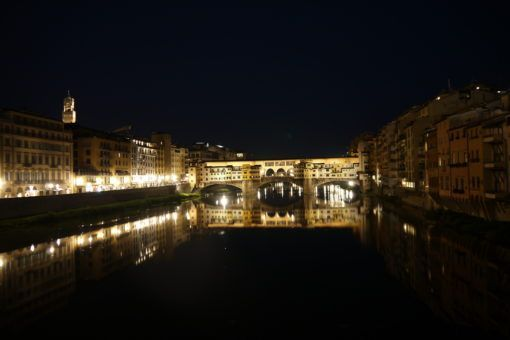 Ponte Vecchio at night, lights reflecting off the Arno river