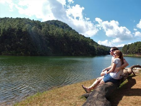 Us sitting on a log in Pang Ung reservoir, Northern Thailand