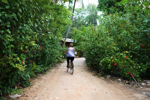 Amy cycling down the road in Polonnaruwa, Sri Lanka