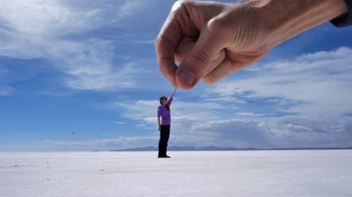 Salt Flats perspective photo - big hand picking up a small person