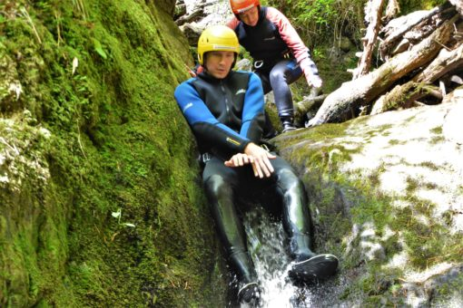 Andrew sliding down rocks on a canyoning trip in Scotland with ACE Adventures