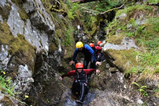 Scrambling along the river on a canyoning trip in Scotland