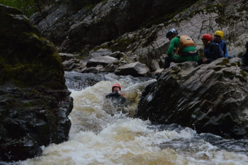 Sliding down a rapid on the Findhorn River in Scotland on a rafting trip with ACE Adventures
