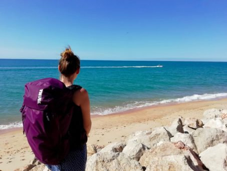 Amy carrying the 35L Thule AllTrail backpack by the sea