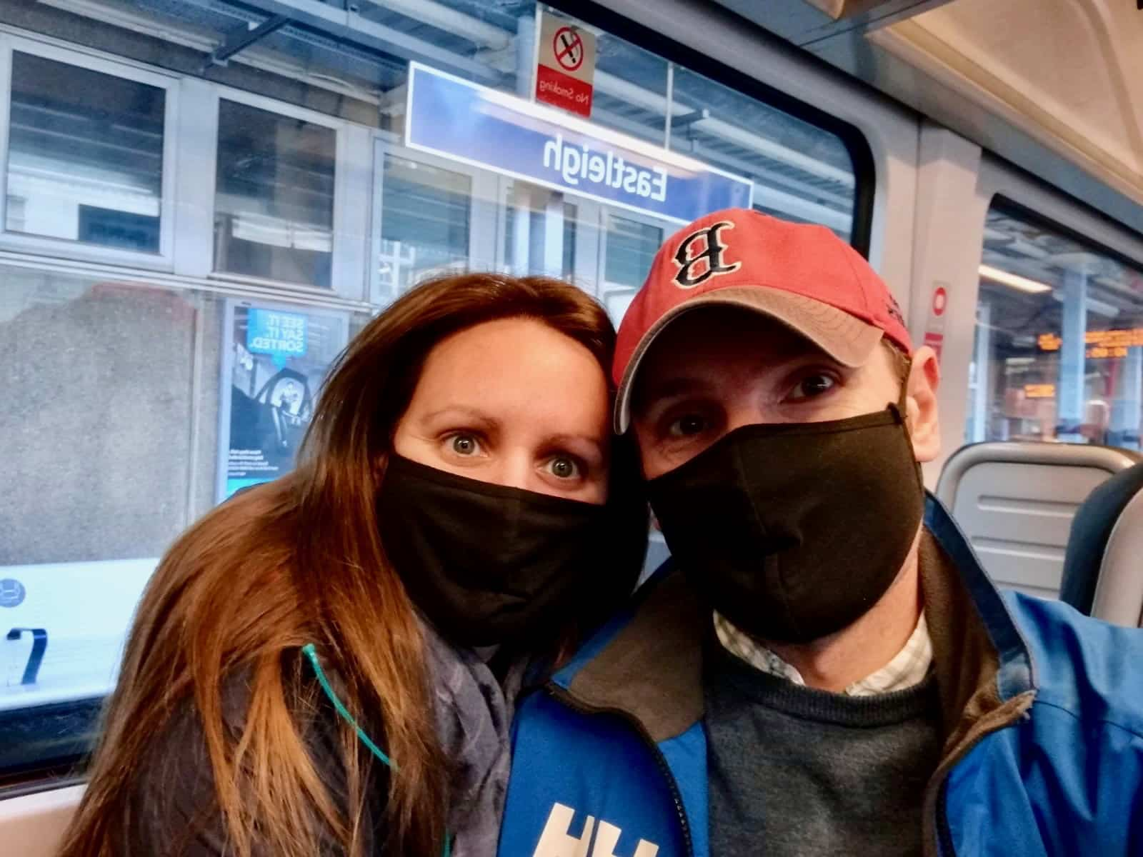 Us with Covid masks on the train to the airport